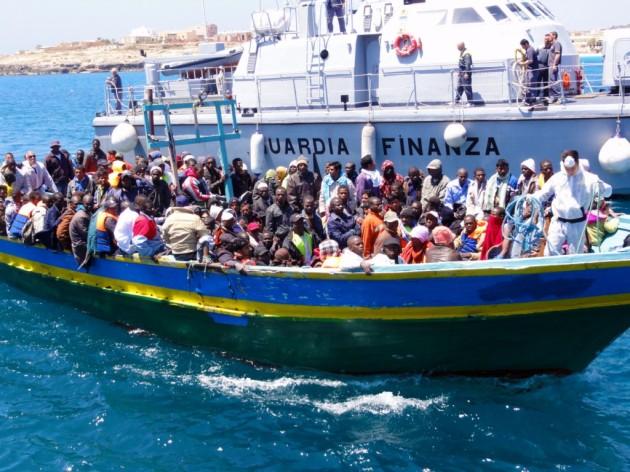Lampedusa-Barca-di-migranti-viene-aiutata-ad-attraccare-dalla-nave-della-Guardia-di-Finanza
